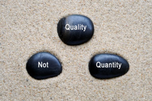 Quality not quantity quotes on zen stones with sand background.